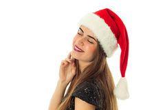 Happy lovely woman in santa hat. Portrait of happy lovely woman in santa hat with closed eyes smiling on camera in studio isolated on white Stock Images
