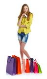 Happy lovely woman with shopping bags and credit card over white Royalty Free Stock Image