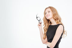 Happy lovely young businesswoman holding glasses and thinking Stock Image