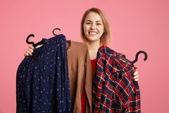Happy lovely young woman holds clothes on hangers, rejoices new purchase, doesn`t know what to choose, going to spend money on new royalty free stock image