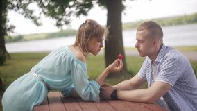Happy lover on a date by the river. Girl feeds boyfriend strawberries. A couple in love on a date sit on a table in front of a river. The guy is hugging the girl stock video footage