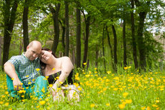 Happy lovers in a buttercup field. Happy young couple is sitting in a field of buttercups Stock Photography