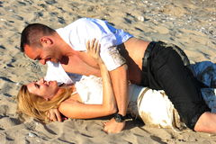 Happy lovers couple - trash the dress. Young happy newlyweds embraced on the beach stock images