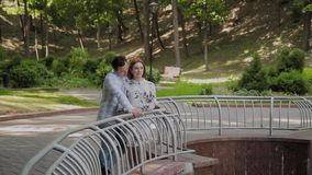 Happy lovers cuddle by the fountain fence. Happy lovers cuddle by the fountain fence stock video