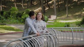 Happy lovers cuddle by the fountain fence. Happy lovers cuddle by the fountain fence stock video footage