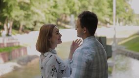Happy lovers cuddle by the fountain fence. Happy lovers cuddle by the fountain fence stock footage