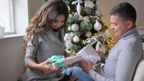 Happy lovers cuddle with New Year`s gifts on background of decorated fir tree. Happy lovers cuddle with New Year`s gifts on the background of decorated fir tree stock video