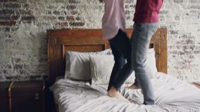 Happy lovers are dancing on bed holding hands and enjoying married life together. Modern double bed, brick wall and. Happy young lovers are dancing on bed stock footage