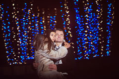 Happy lovers embrace on a background of glowing blue hearts.  Royalty Free Stock Images