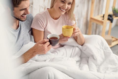 Happy lovers enjoying hot beverage in bedroom Stock Photography