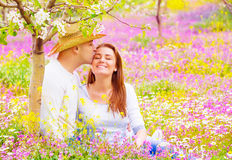 Happy lovers kissing outdoors. Romantic date in blooming garden, beautiful young family, affection and love concept Stock Images