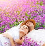 Happy lovers on lavender glade. Handsome men with attractive women lying down on fresh lavender field, enjoying each other, romantic relationship, love concept Stock Images