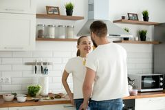 Happy lovers looking in eyes enjoying intimacy cooking breakfast. Happy young lovers enjoy morning intimacy in kitchen together looking in eyes, romantic men and royalty free stock images