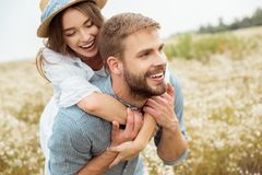 happy lovers piggybacking together in filed royalty free stock image