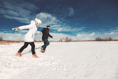 Happy lovers running through the snow. Concept of happy family life, winter holidays, hike. girlfriend ans boyfriend runnning on snowy field over beautiful blue Royalty Free Stock Photo