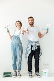 Happy lovers showing thumb up while making repair Stock Image