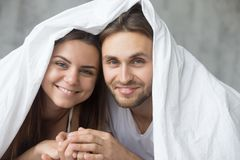 Happy lovers smiling having fun under warm blanket royalty free stock image
