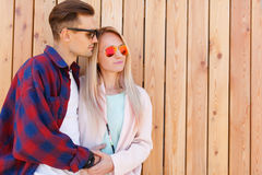 Happy lovers in sunglasses embrace. On background of wooden fence Stock Photo