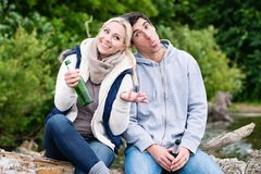 Lovers in vacation sitting at waterside clinking beer bottles Royalty Free Stock Photos