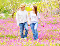 Happy lovers walking outdoors. Happy smiling lovers holding hands and looking each other walking on pink floral field, enjoying family, romance and love concept Stock Photo