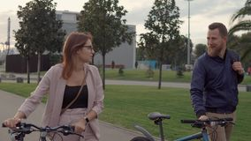 Happy lovers are walking together in park, rolling their bikes near stock footage