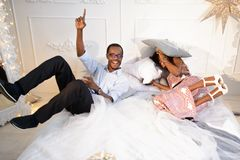 The happy loving afro-american couple is getting crazy on the Christmas eve near the New Year tree, they are lying on. The bed ang laughing a lot Royalty Free Stock Images