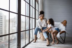 Happy loving afro american family. Young mother and her daughter playing in the nursery. Mom and daughter are dancing on the. Background of a large window royalty free stock photography