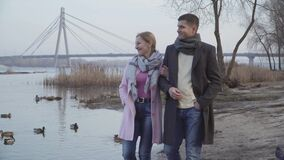 Happy loving Caucasian couple with age difference walking along riverbank in city park. Portrait of positive adult man