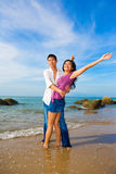 Happy loving couple. Hugging each on the beach with bright blue sky Royalty Free Stock Photography