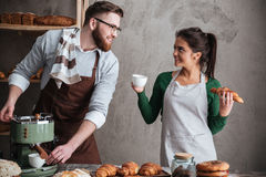 Happy loving couple bakers drinking coffee Royalty Free Stock Photo
