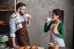 Happy loving couple bakers drinking coffee Stock Image