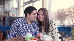 Happy loving couple in cafe laughing, drinking tea. using tablet for fun. First date. Happy loving couple in cafe laughing, drinking tea, using tablet for fun stock footage