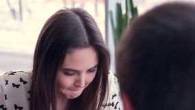 Happy loving couple in cafe talking. Young emotional girl close up. stock video footage