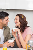 Happy loving couple with coffee cup in kitchen Stock Photography