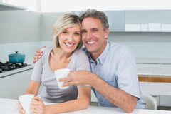 Happy loving couple with coffee cups in kitchen Royalty Free Stock Photo
