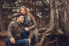 Happy loving couple on the cozy walk in autumn forest. Sitting near pine tree roots Stock Photo