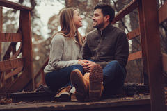 Happy loving couple on the cozy walk in autumn forest. Sitting near pine tree roots Stock Photography