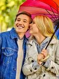 Happy loving couple on a date under umbrella Stock Photos
