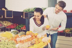 Happy loving couple deciding on fruits in shop royalty free stock photography