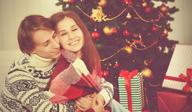 Happy loving couple in embrace warmed at Christmas tree Royalty Free Stock Photography