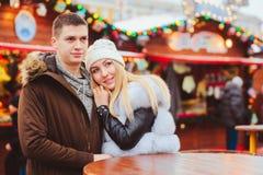 Happy loving couple enjoying Christmas or New year Holidays outdoor, walking on city festive market. With street food stock photos