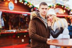 Happy loving couple enjoying Christmas or New year Holidays outdoor, walking on city festive market. With street food stock photo