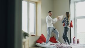 Young happy and loving couple fight pillows in bed at home in the morning Royalty Free Stock Images