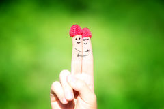 Happy loving couple of fingers with raspberries and painted smil Royalty Free Stock Photos