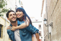Happy loving couple. Happy young man piggybacking his girlfriend. Happy loving couple. Happy young men piggybacking his girlfriend while hug he Royalty Free Stock Photography