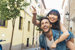 Happy loving couple. Happy young man piggybacking his girlfriend. Happy loving couple. Happy young men piggybacking his girlfriend while pointing out at front Stock Photography