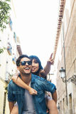 Happy loving couple. Happy young man piggybacking his girlfriend. Happy loving couple. Happy young men piggybacking his girlfriend while pointing out at front Stock Image