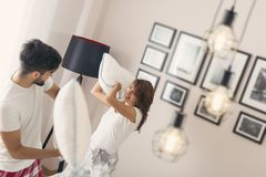Pillow fight. Happy loving couple having fun having a pillow fight in bed Stock Images