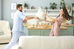 Happy loving couple having fun while having a pillow fight in the living room stock image