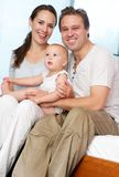 Happy loving couple holding cute baby at home Stock Images